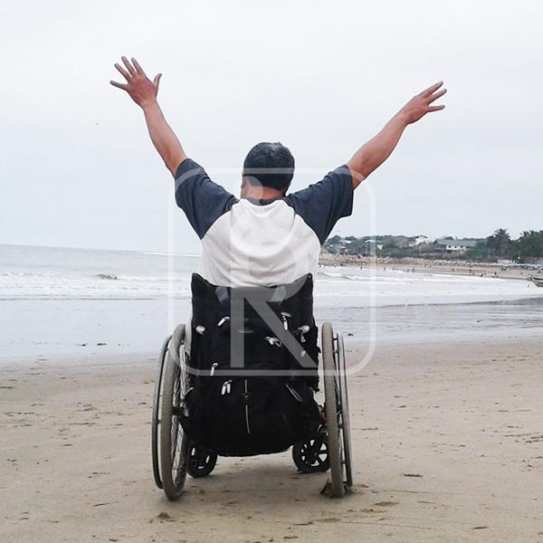Persona con discapacidades paseando en la playa