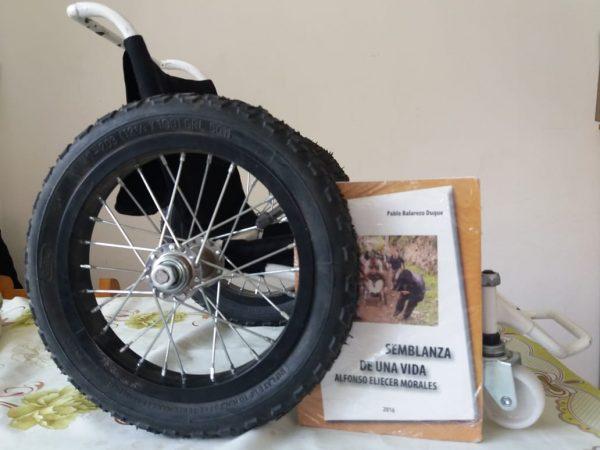 """Silla de ruedas y libro """"Semblanzas de una vida"""". Foto por: REDTA-EC"""